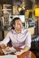 Hispanic businessman using cell phone in coffee shop 11018073763| 写真素材・ストックフォト・画像・イラスト素材|アマナイメージズ