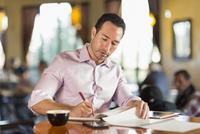 Hispanic businessman writing in coffee shop 11018073764| 写真素材・ストックフォト・画像・イラスト素材|アマナイメージズ