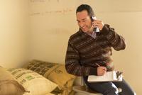 Hispanic entrepreneur talking on telephone in store