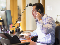 Hispanic businessman talking on telephone in office