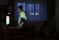 Caucasian couple using computer at night