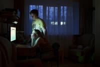 Caucasian couple using computer at night
