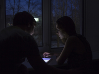Caucasian couple using digital tablet at night