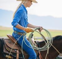 Caucasian cowgirl holding lasso on horseback