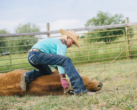 Cowgirl tying cattle on ranch