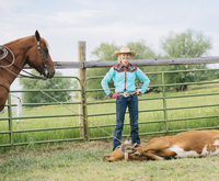 Cowgirl smiling with tied cattle on ranch 11018073833| 写真素材・ストックフォト・画像・イラスト素材|アマナイメージズ