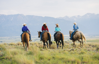 Cowboy and cowgirls riding horseback on ranch