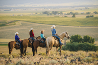 Cowboy and cowgirls on horseback admiring rural landscape