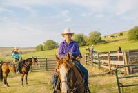 Cowboy riding horseback on ranch