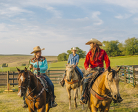 Cowgirls riding horseback on ranch