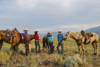 Cowboy and cowgirls with horses on ranch