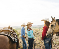 Cowgirls with horses on ranch