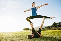 Caucasian couple doing acro yoga in park 11018073864| 写真素材・ストックフォト・画像・イラスト素材|アマナイメージズ