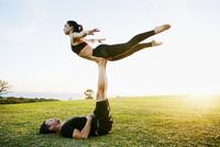 Caucasian couple doing acro yoga in park 11018073866| 写真素材・ストックフォト・画像・イラスト素材|アマナイメージズ