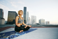 Mixed race woman meditating on urban rooftop