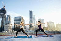 Women practicing yoga on urban rooftop