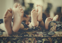 Close up of feet of children on sofa