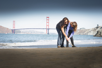 Mother and daughter drawing in sand on beach, San Francisco, California, United States