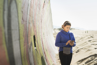 Mixed race girl using cell phone on beach