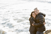 Couple hugging near ocean waves