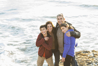 Family hugging near ocean waves