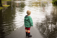 Caucasian boy wearing puddles near flood