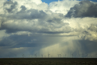 Storm clouds over wind turbines in rural landscape