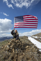 Caucasian woman planting American flag on remote hilltop