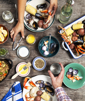 High angle view of hands at seafood dinner