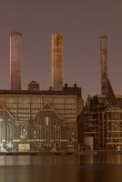 Factory smokestacks lit up at night