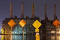 Warning signs and factory smokestacks lit up at night