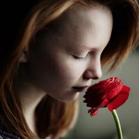 Caucasian teenage girl smelling flower