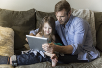 Father and daughter using digital tablet on sofa