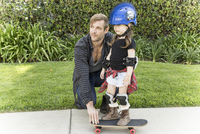 Father teaching daughter to skateboard