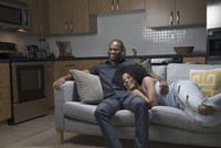 African American couple relaxing on sofa