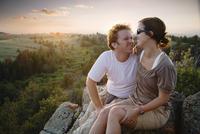 Caucasian couple hugging on remote hilltop