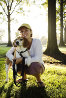 Caucasian woman hugging dog in park 11018074123| 写真素材・ストックフォト・画像・イラスト素材|アマナイメージズ