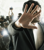 Young male celebrity shielding face from photographers 11018074500| 写真素材・ストックフォト・画像・イラスト素材|アマナイメージズ