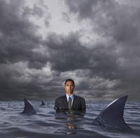 Hispanic businessman standing in water with sharks 11018074528| 写真素材・ストックフォト・画像・イラスト素材|アマナイメージズ
