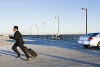 African businessman running to catch plane at airport 11018077744| 写真素材・ストックフォト・画像・イラスト素材|アマナイメージズ