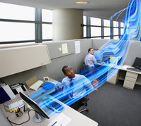 Businessmen watching light stream between computers in office 11018078285| 写真素材・ストックフォト・画像・イラスト素材|アマナイメージズ