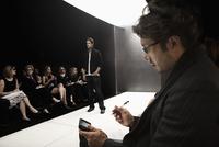 People watching model on runway in fashion show 11018078743| 写真素材・ストックフォト・画像・イラスト素材|アマナイメージズ