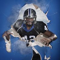 African American football player breaking through wall 11018080012  写真素材・ストックフォト・画像・イラスト素材 アマナイメージズ
