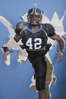 African American football player breaking through wall 11018080013  写真素材・ストックフォト・画像・イラスト素材 アマナイメージズ