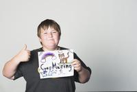 Boy holding sign gesturing thumbs-up 11018080128  写真素材・ストックフォト・画像・イラスト素材 アマナイメージズ
