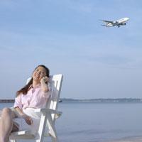 砂浜でイスに座り携帯電話で話をしているビジネスウーマン
