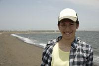 海と帽子を被った日本人男性