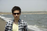 海とサングラスをかけた日本人男性