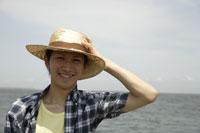 海と麦わら帽子を被った日本人男性