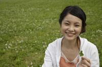 四葉のクローバーを持つ日本人女性